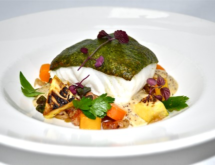 -Roast cod fish coated with parsley crust, served with classic choucroute, blanche carrots, celeriac, fried potato, mussel fume and wole grain mustard sauce.