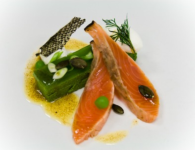 -Cured smoked salmon fillet served on a spinach bavaroi, covered with a thin parsley glee, horseradish, lemon zest, honey cream, baked salmon skin as a crispy tuile, lemon and cucumber balls.